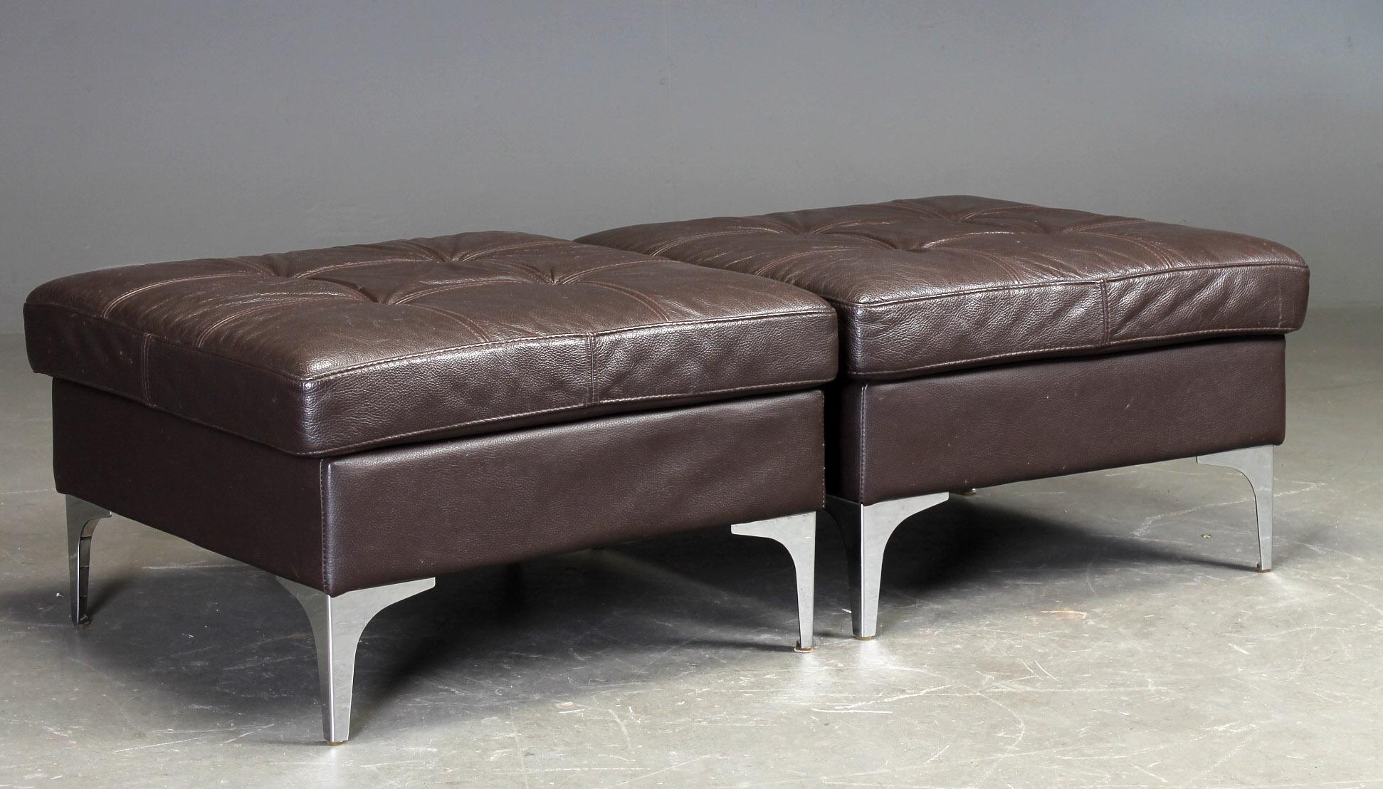 Dansk møbelproducent. To puf - Dansk møbelproducent. To puf betrukket med dybthæftet brunt læder, på ben af forkromet metal. H. 43. 72 x 72 cm