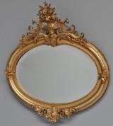 Ovalt spejl i ramme af guldbronzeret træ og gesso. Ca. 1900