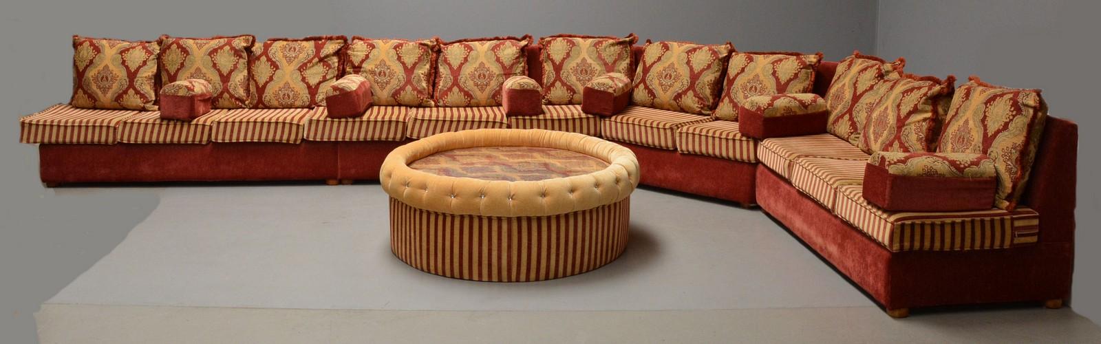 Modulsofa i arabisk stil - Modulsofa i arabisk stil. Polstret med mønstret møbelstof. Hertil puf / sofabord samt talrige puder i tilsvarende stil. Mål som opstillet; L 550, B 330, H 83 cm. Fremstår med brugsspor