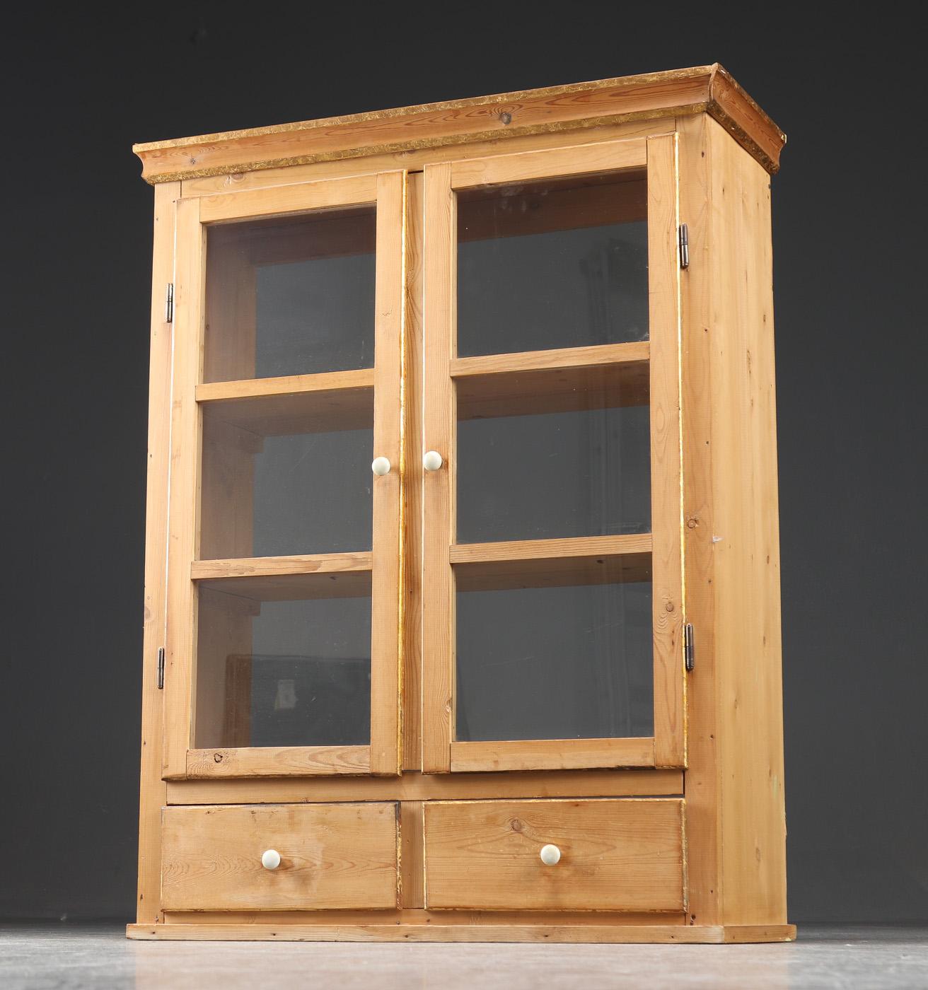 Køkkenskab af fyr, 1900-tallets begyndelse - Køkkenskab af fyr med to vitrinedøre, forneden to skuffer, greb af porcelæn, 1900-tallets begyndelse. H. 115 B. 90 D. 32 cm. Brugsspor; ridser og skrammer