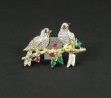 Broche af guld med rubiner, smaragder og brillanter, ca. 1.05 ct.