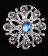 A pair of earrings, large rosettes, 18 kt. white gold with blue moonstone and diamonds, total approx. 3.80 ct. (2)