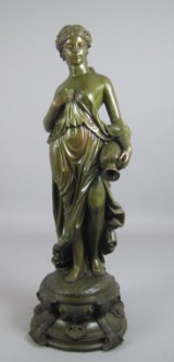 A bronze sculpture of a lady with jug on lotus plinth
